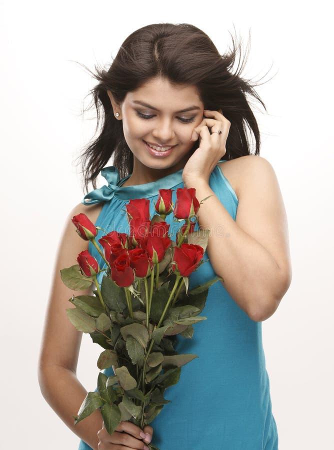 Schönes Mädchen mit roten Rosen lizenzfreie stockbilder