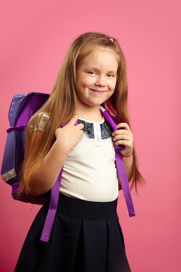 Schönes Mädchen mit Rucksack auf ihren Schultern steht auf lokalisiertem rosa Hintergrund, hat gute Laune, schaut vorwärts glückl lizenzfreie stockfotos