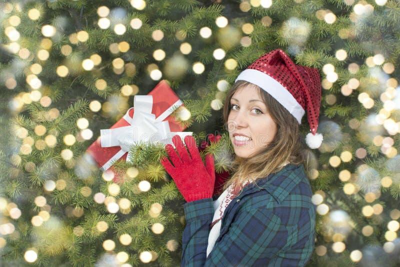 Schönes Mädchen mit Santa Claus-Hut, der ihr Geschenk nimmt stockbild