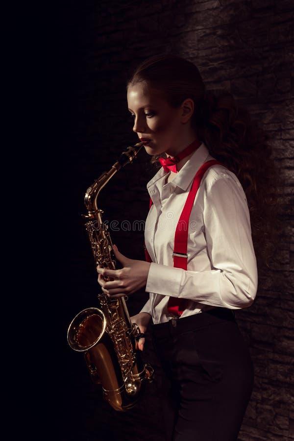 Schönes Mädchen mit Saxophon im Kleid der Männer stockbilder