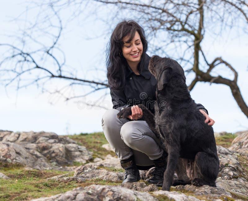 Schönes Mädchen mit schwarzem Hund des Köters auf Bergen lizenzfreie stockfotografie