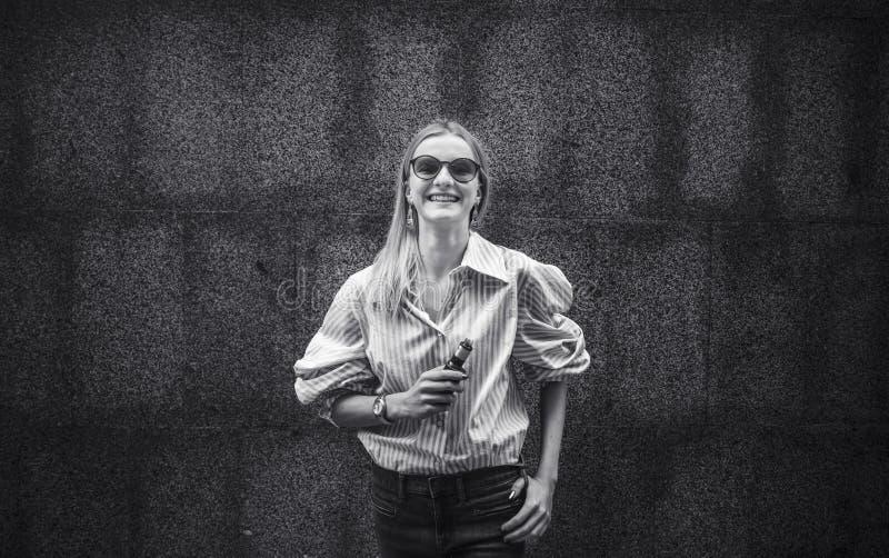 Schönes Mädchen mit Vergnügen raucht ein vape, den Tag, im Freien stockfotos