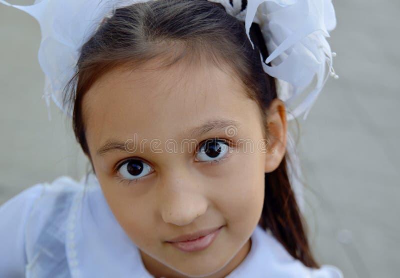 Schönes Mädchen mit weißen Bögen, Schulmädchenporträt lizenzfreie stockbilder