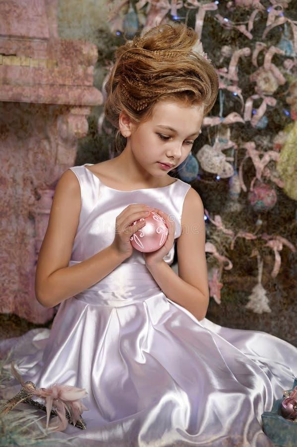 Schönes Mädchen mit Weihnachtsrosaball lizenzfreie stockfotos