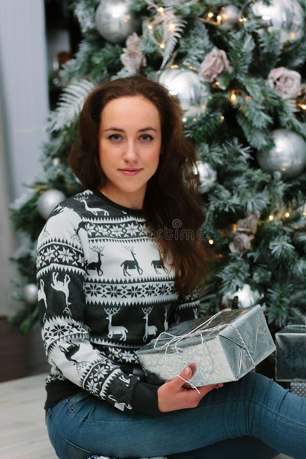 Schönes Mädchen oder junge Frau, die nahe dem Weihnachtsbaum sitzen lizenzfreies stockbild