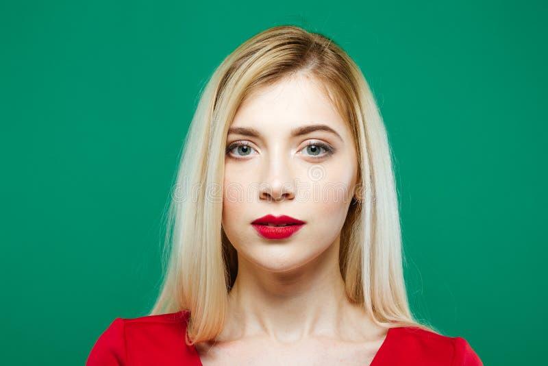Schönes Mädchen-Porträt im Studio auf grünem Hintergrund Nette junge Frau wirft auf, die Kamera betrachtend lizenzfreie stockbilder