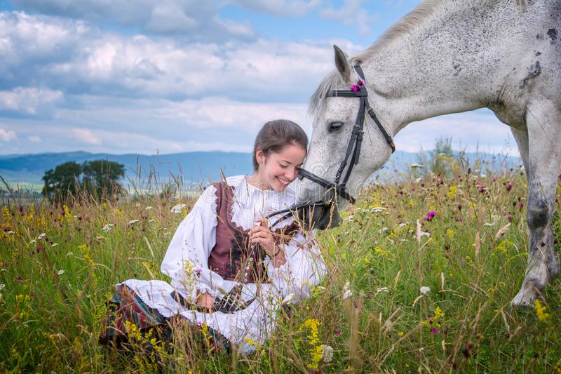 Schönes Mädchen Rumäniens und traditionelles Kostüm in der Sommerzeit und im schönen arabischen Pferd lizenzfreie stockfotografie