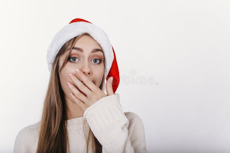 Schönes Mädchen in Sankt-Hut, der ihren Mund durch handYoung europäische Frau in Sankt-Hut eigenhändig bedeckt ihren Mund bedeckt lizenzfreie stockfotos