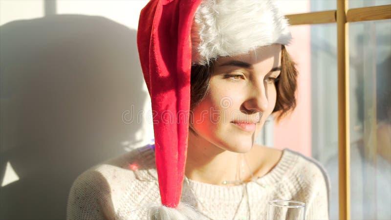 Schönes Mädchen in Santa Claus-Hut mit einem Glas Champagner schauend aus dem Fenster, dem fröhlichen Christmass und dem neuen Ja stockfoto