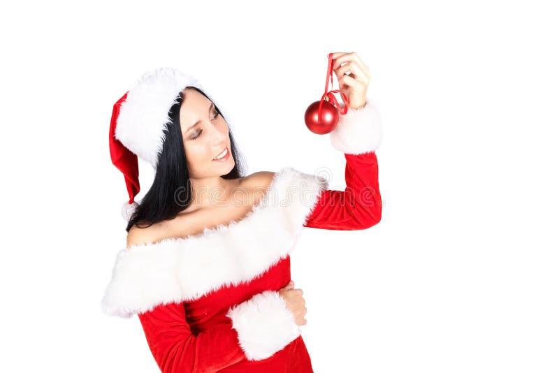 Schönes Mädchen Santa Claus mit dem dunklen Haar in der Klage auf weißem Hintergrund hält das Balldekorationsrot auf weißem Hinte stockbild
