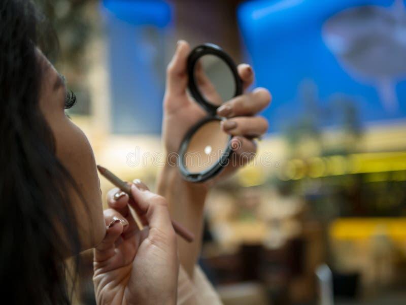 Schönes Mädchen schaut in einem kleinen Spiegel und malt ihre Lippen mit einer Lippenzwischenlage lizenzfreies stockbild