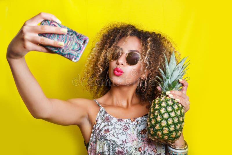Schönes Mädchen selfie mit einem Smartphone Schöne junge Afroamerikanerfrau mit Afrofrisur und Sonnenbrille stockfotos
