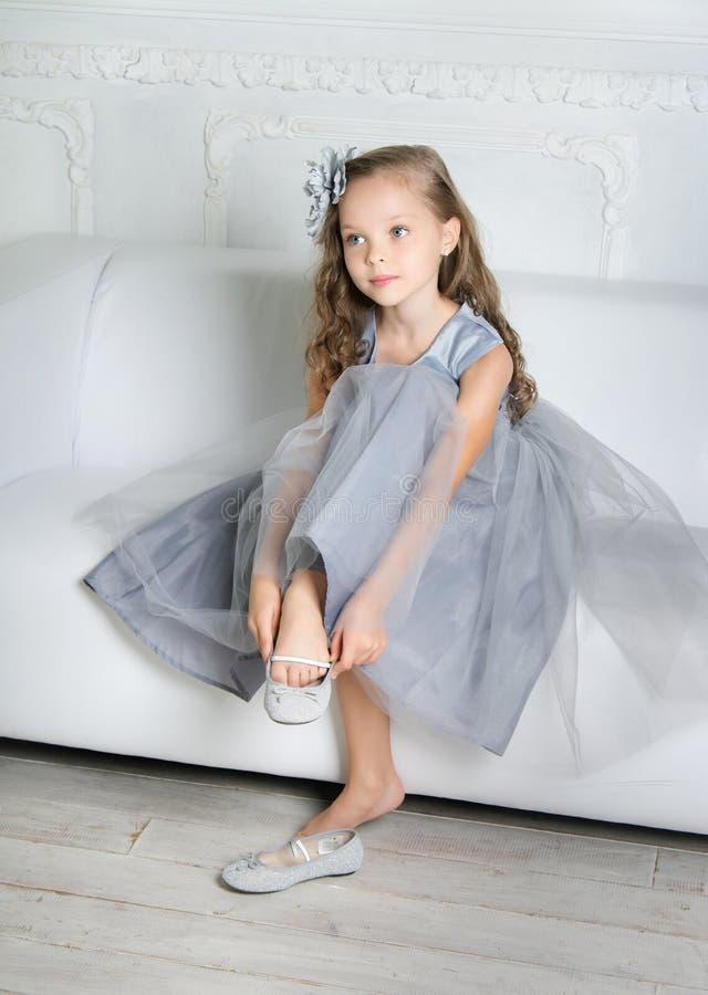Schönes Mädchen sitzt auf dem Sofa lizenzfreie stockfotos