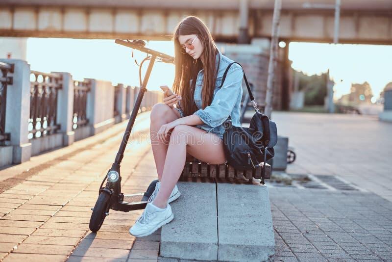 Schönes Mädchen sitzt auf der Bank mit ihrem Roller stockbild