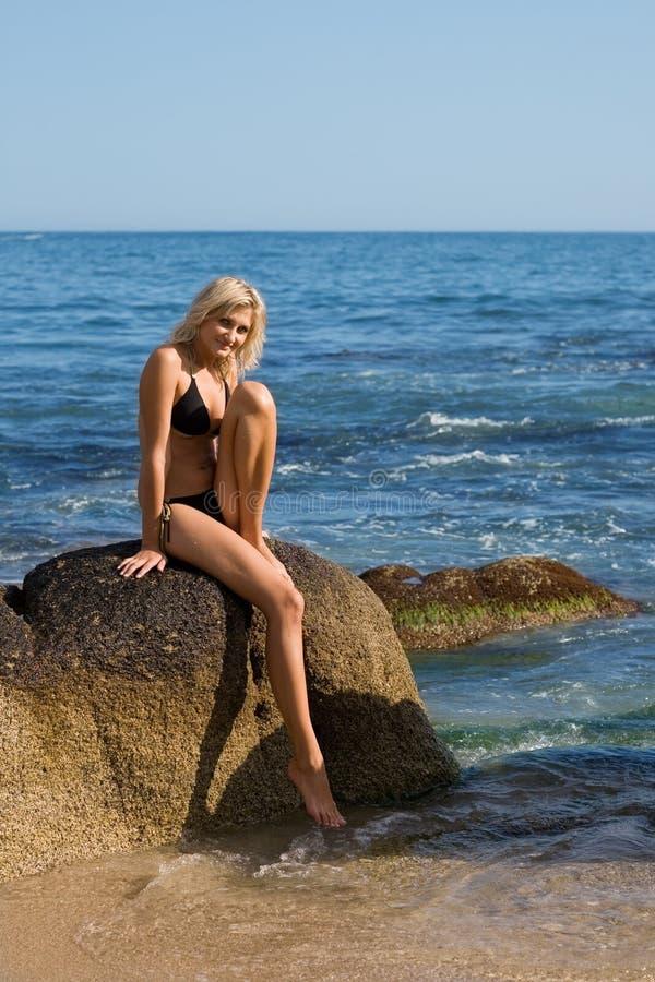 Schönes Mädchen sitzt auf einem Felsen lizenzfreie stockfotografie
