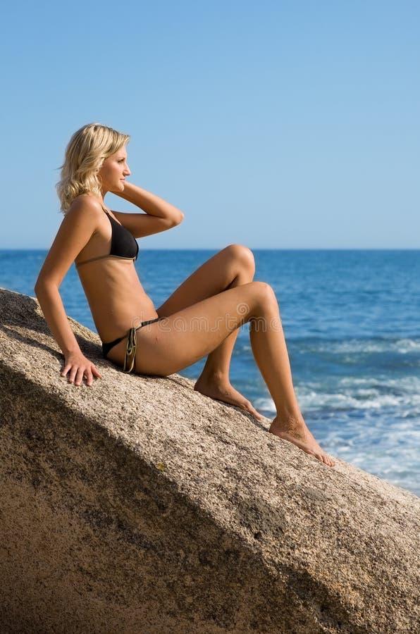 Schönes Mädchen sitzt durch das Meer stockbild