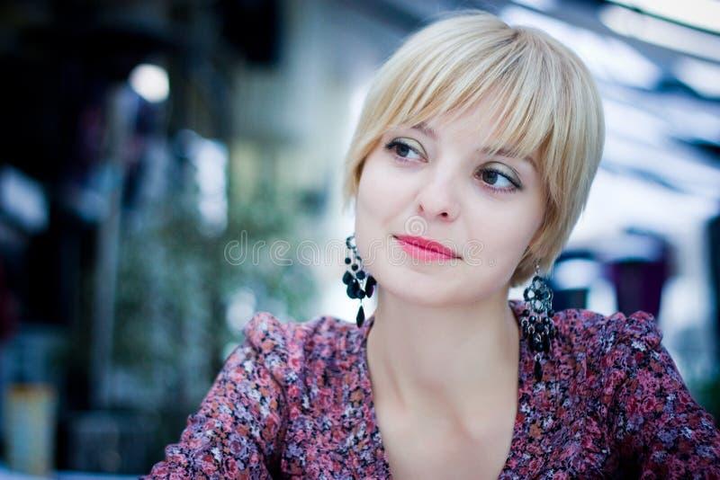 Schönes Mädchen sitzt in einem Café stockbilder