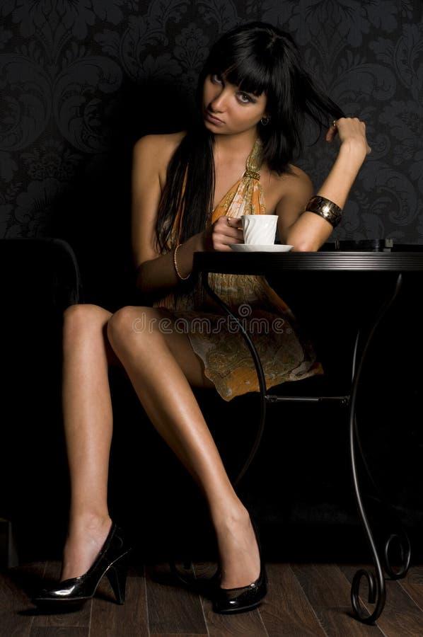 Schönes Mädchen sitzt im Kaffee stockbild