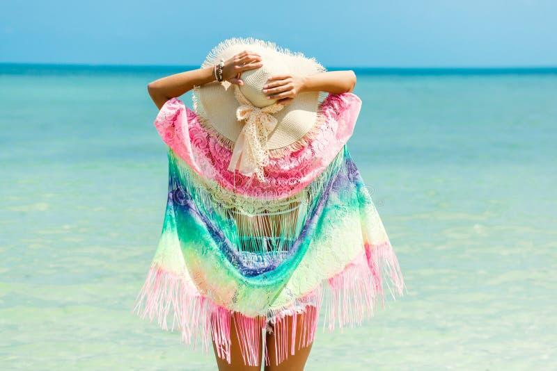 Schönes Mädchen steht auf dem Strand durch das Meer, tragende Sonnenbrille eines pareo Strohhutes, Hände in der Seitengeste der F lizenzfreies stockfoto