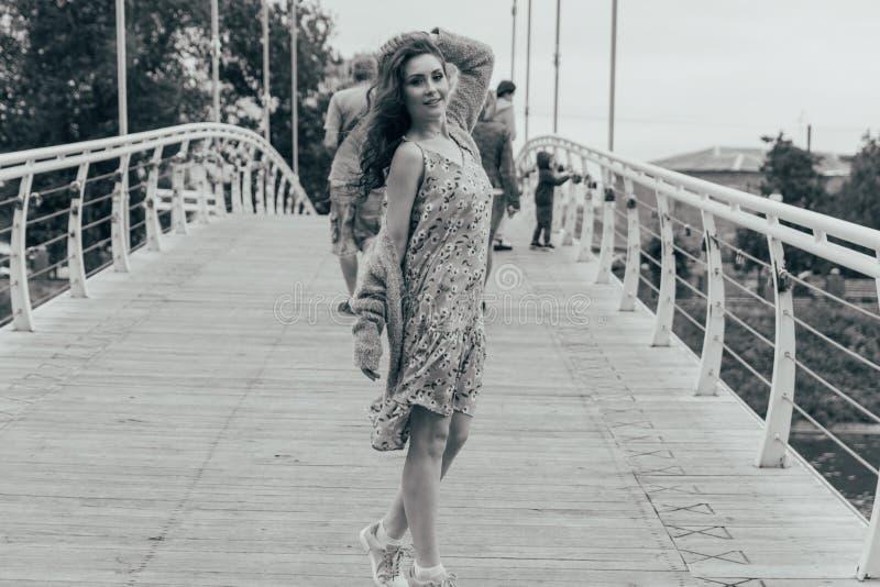 Schönes Mädchen steht auf der Brücke, der Wind durchbrennt in ihrem Gesicht und entwickelt ihr Haar Auf Tabelle ist ein blauer Va stockbild