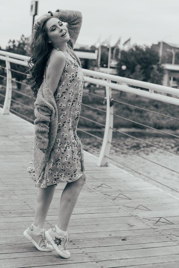 Schönes Mädchen steht auf der Brücke, der Wind durchbrennt in ihrem Gesicht und entwickelt ihr Haar Auf Tabelle ist ein blauer Va stockfotografie