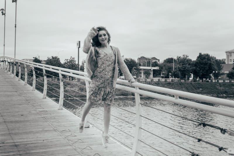 Schönes Mädchen steht auf der Brücke, der Wind durchbrennt in ihrem Gesicht und entwickelt ihr Haar Auf Tabelle ist ein blauer Va stockfotos