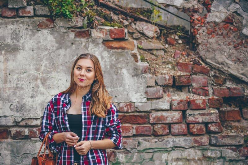 Schönes Mädchen steht gegen Backsteinmauer lizenzfreies stockfoto