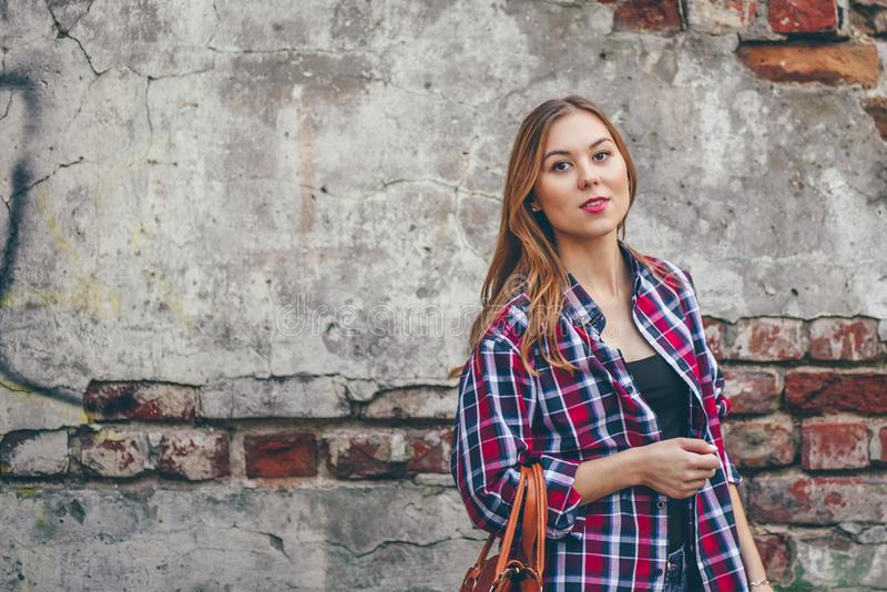 Schönes Mädchen steht gegen Backsteinmauer lizenzfreie stockfotografie