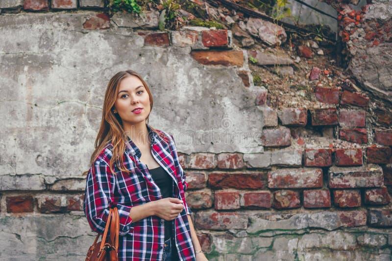 Schönes Mädchen steht gegen Backsteinmauer stockfotos