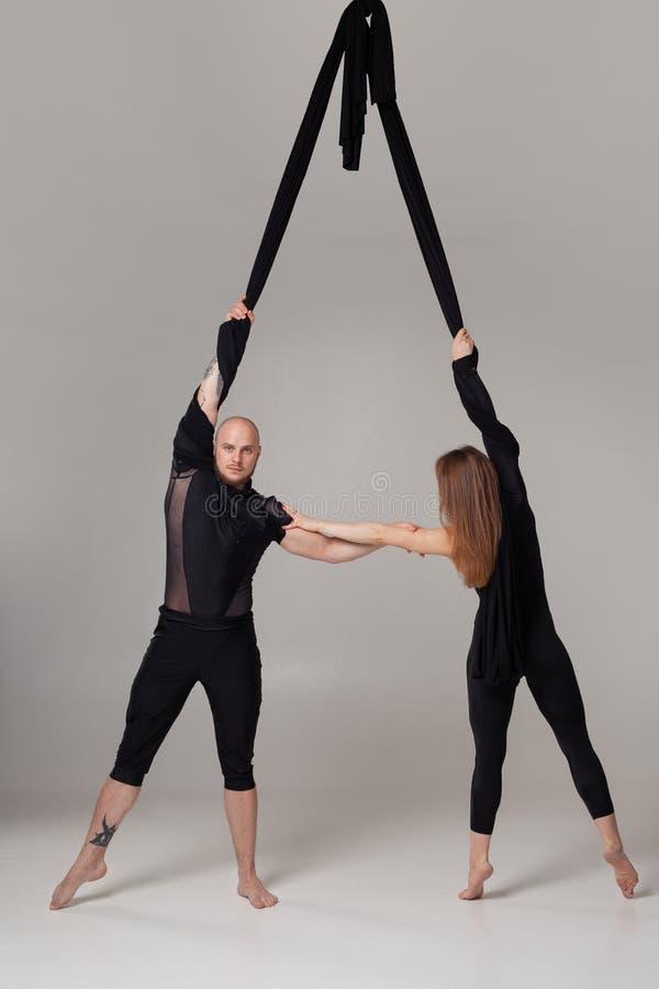 Schönes Mädchen und ein athletischer Mann Anzügen eines in den schwarzen Sports sind die Ausführung akrobatische Elemente in eine stockfotos