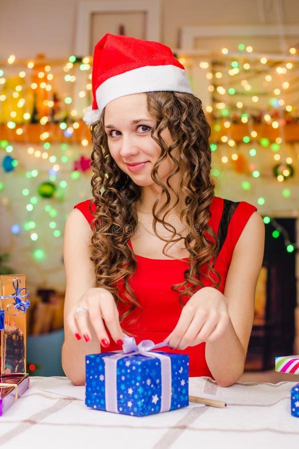 Schönes Mädchen verpackt ein Geschenk stockbilder