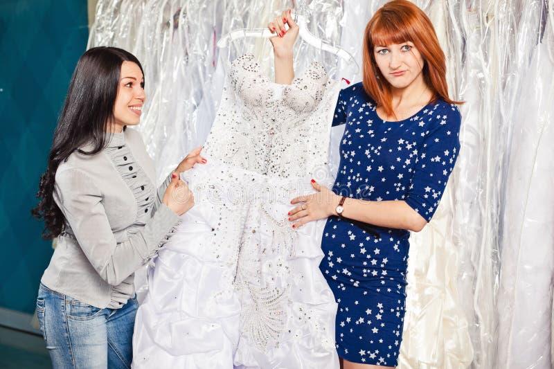 Schönes Mädchen wählt ihr Hochzeitskleid Porträt in Brautsa lizenzfreie stockfotos
