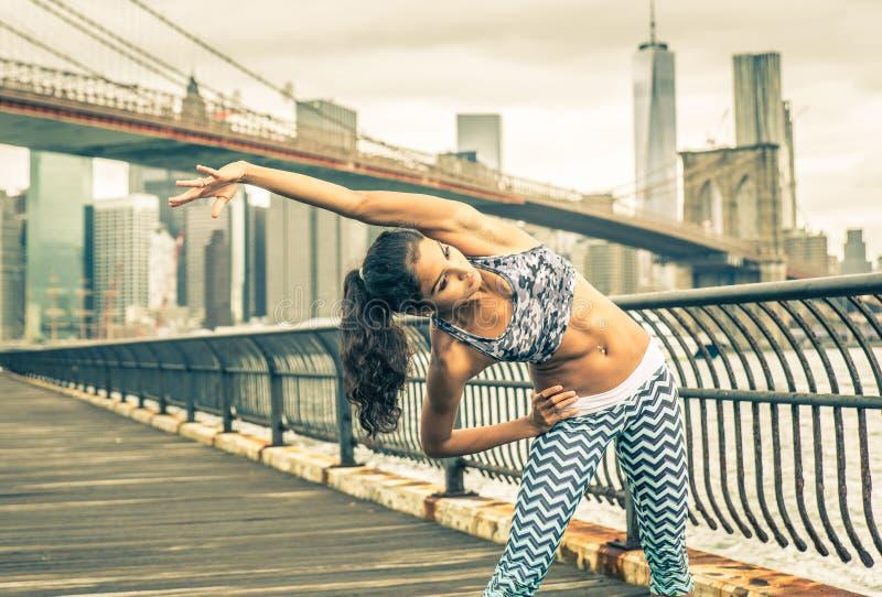 Schönes Mädchen, welches das Ausdehnen vor intensivem Betrieb in New York City macht lizenzfreie stockfotografie