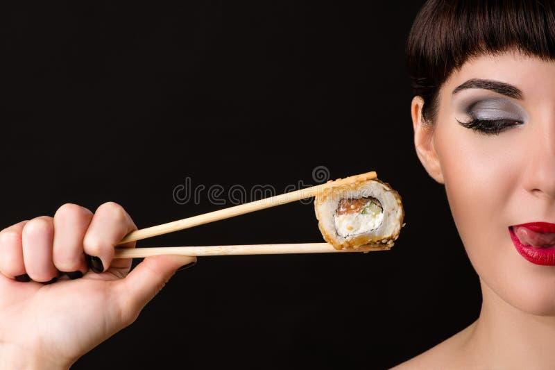 Schönes Mädchen, welches das Schauen auf köstlicher Rolle leckt lizenzfreie stockfotos