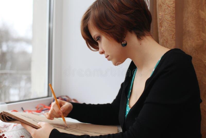 Schönes Mädchen zeichnet Skizzen stockfoto