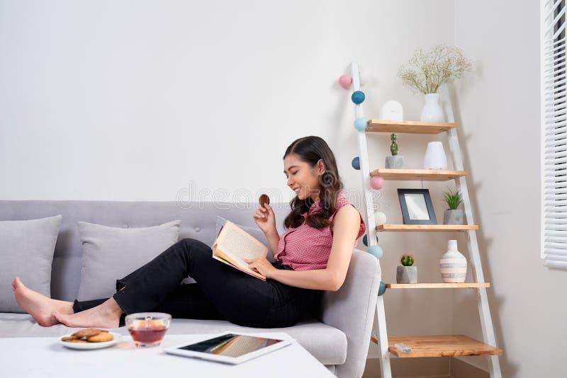 Schönes Mädchen zu Hause, das auf der Couch, dem Lesebuch und dem ha sitzt stockfotografie