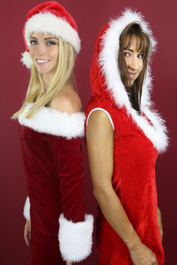 Schönes Mädchen zwei, das Santa Costume trägt lizenzfreie stockfotos
