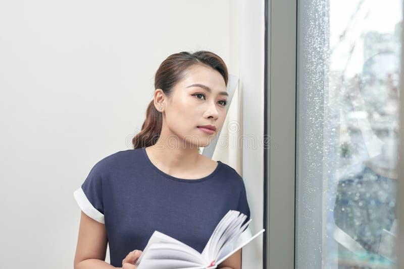 Schönes Mädchenlesebuch nahe Fenster zu Hause Entspannende und Ablesenbuch Frau auf Fensterbrett stockbilder