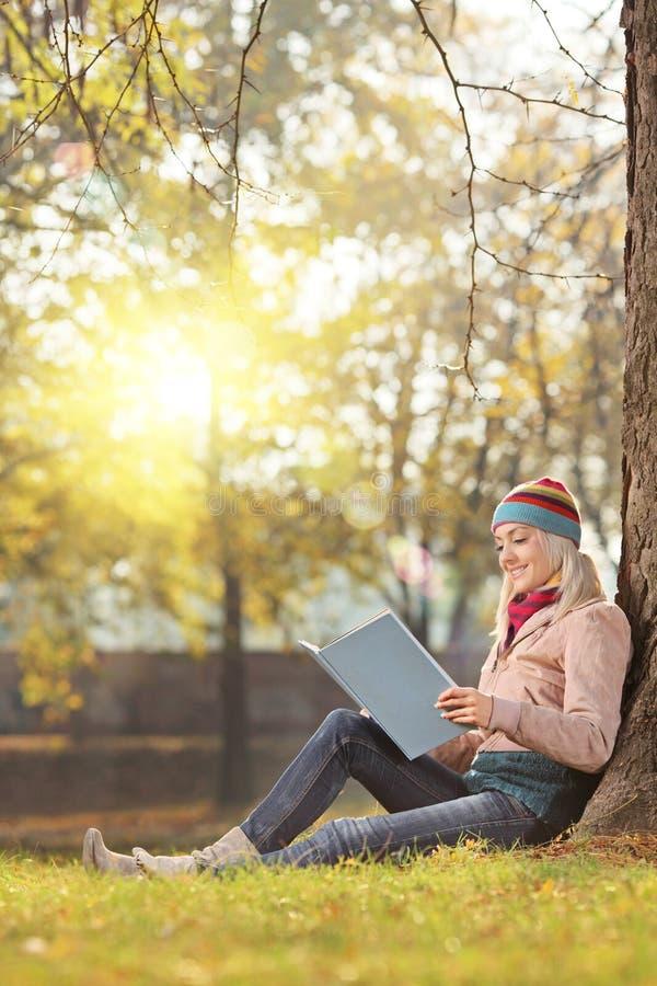 Schönes Mädchenlesebuch und Genießen eines sonnigen Tages in einem Park lizenzfreies stockfoto