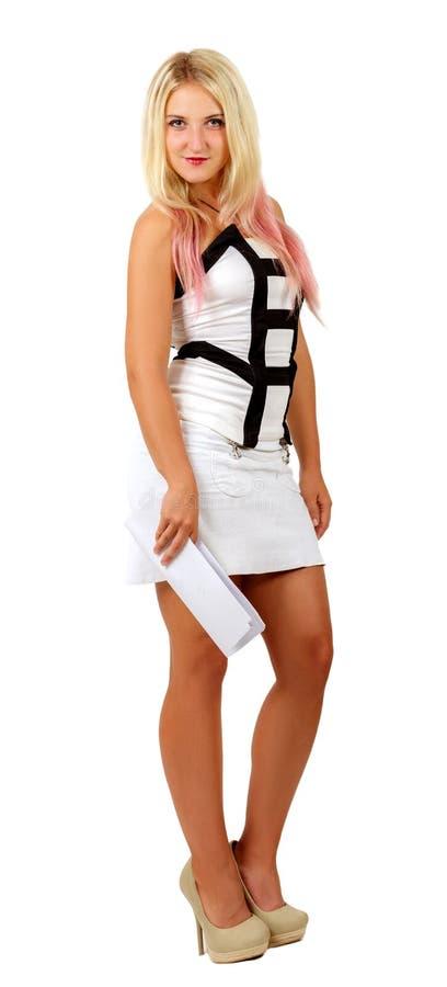 Schönes Mädchenmodell im weißen Kleid auf hohen Absätzen haltenen Dokumenten in den in voller Länge und Betrachten der Kamera stockfotos