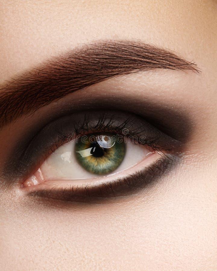 Schönes Makrofoto des Frauenauges mit schwarzem rauchigem Make-up Perfekte Formaugenbrauen Kosmetik und Verfassung stockbilder