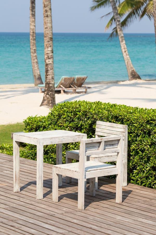 Schönes Meer, KokosnussPalme, Holztisch und Stühle lizenzfreies stockbild