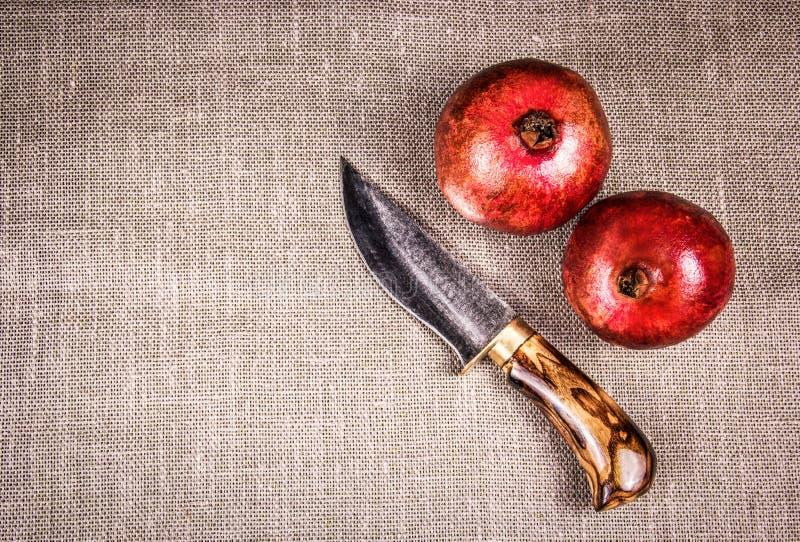 Schönes Messer mit Holzgriff und zwei reifen Granatäpfeln Handmesser und -granaten stockbilder