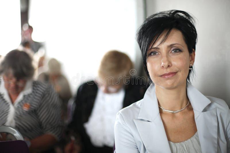 Schönes mittel-gealtertes Frauenporträt am Konferenzsaal stockfoto