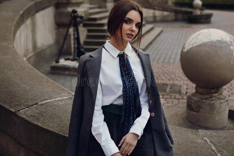 Schönes Mode-Mädchen in der modernen Kleidung, die in der Straße aufwirft stockfotografie