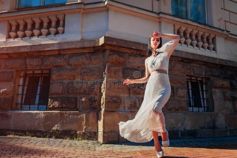Schönes Mode-Modell, das draußen im weißen Hochzeitskleid aufwirft Tragendes Zubehör und Schmuck der jungen Frau stockfotografie