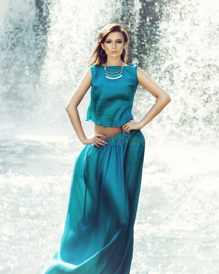 Schönes Mode-Modell, das vor dem Wasserfall aufwirft stockbilder