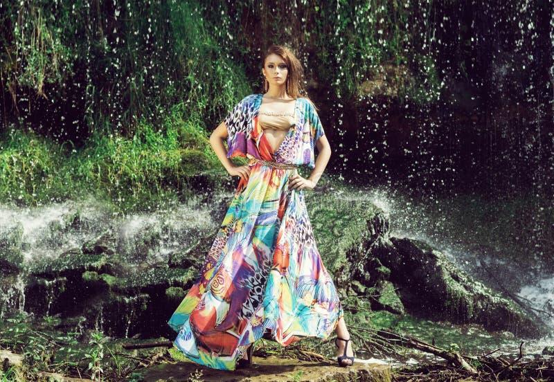 Schönes Mode-Modell, das vor einem Wasserfall aufwirft stockbild
