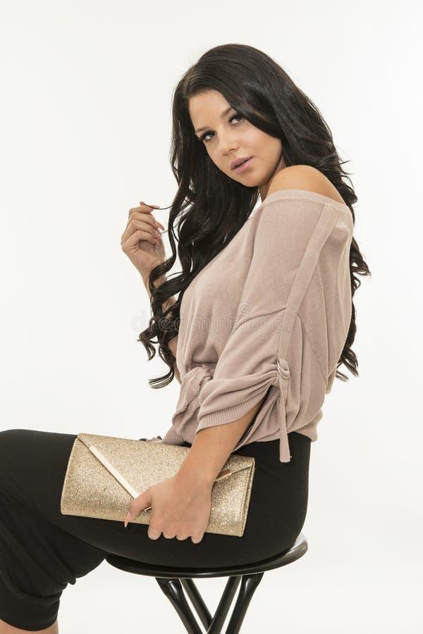 Schönes Mode-Modell-Mädchen, das eine goldene Handtasche hält lizenzfreies stockfoto