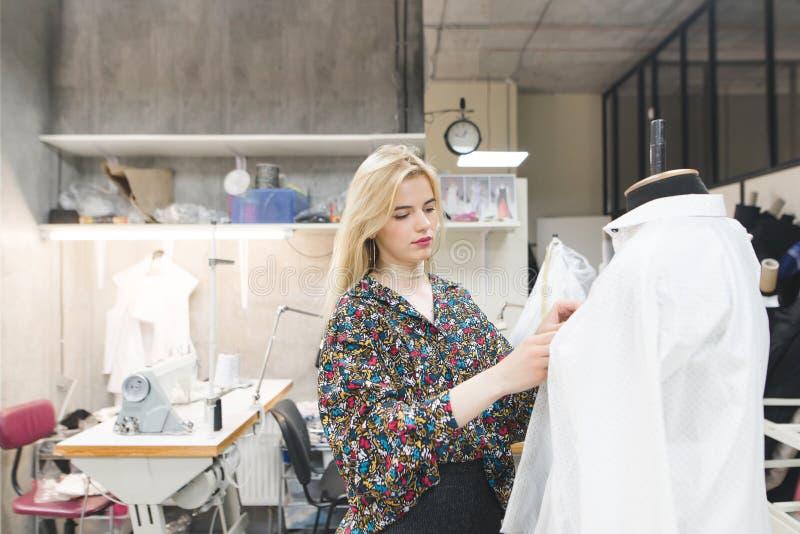 Schönes Modedesignermädchen steht in einem Studio nahe dem Mannequin und repariert Kleidung auf ihm stockbild